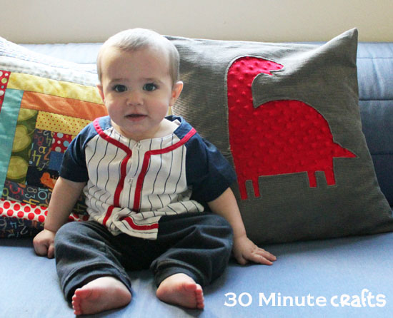baby with dinosaur pillow